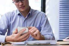 Мобильный телефон пользы бизнесмена на рабочем месте сообщение o человека отправляя СМС Стоковая Фотография