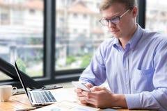 Мобильный телефон пользы бизнесмена на рабочем месте сообщение o человека отправляя СМС Стоковое Изображение