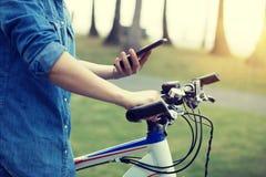 Мобильный телефон пользы велосипедиста пока едущ велосипед в тропическом парке Стоковая Фотография RF