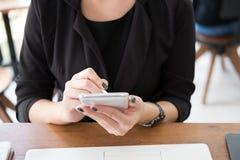 Мобильный телефон пользы коммерсантки на рабочем месте Молодая женщина texting Стоковые Фотографии RF