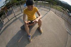 мобильный телефон пользы скейтбордиста стоковая фотография