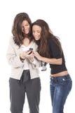 мобильный телефон смотря 2 женщин стоковая фотография