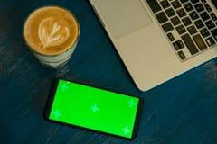 Мобильный телефон с зеленым экраном около горячих кофе и компьтер-книжки на голубой таблице Стоковые Изображения RF