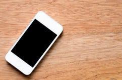 Мобильный телефон с пустым экраном на деревянной предпосылке стоковые фото