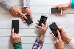Мобильные телефоны в руке друзей стоковые изображения rf