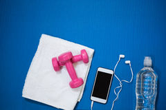 Мобильный телефон, бутылка с водой, полотенце и гантель держали на циновке тренировки Стоковая Фотография