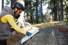 Мобильный телефон велосипедиста горы говоря пока смотрящ карту Стоковые Изображения