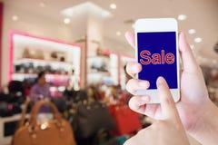 Мобильный телефон владением руки запачканный в предпосылке торгового центра Стоковые Фото