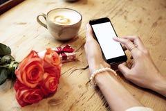 Мобильный телефон в красивых руках женщины Сообщение сочинительства дамы Цветки красных роз и присутствующая коробка позади на де стоковое изображение rf