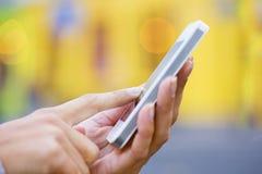 Мобильный телефон в руке женщины, желтой предпосылке магазина Стоковое Фото