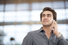 Мобильный телефон молодого бизнесмена говоря в офисе Стоковые Фотографии RF