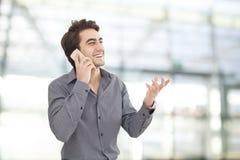 Мобильный телефон молодого бизнесмена говоря в офисе Стоковые Изображения RF