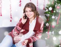 Мобильный телефон молодой женщины говоря около рождественской елки Стоковая Фотография