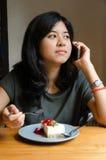 Мобильный телефон молодой женщины говоря с тортом в кафе Стоковые Изображения