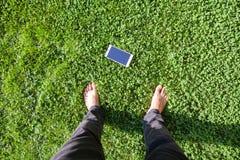 Мобильный телефон находки человека на траве взгляд сверху ноги человека и мобильного телефона на траве Стоковые Фотографии RF