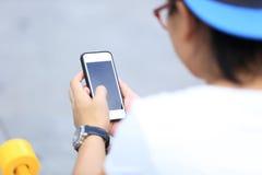 Мобильный телефон пользы скейтбордиста сидит на лестницах города Стоковые Изображения