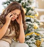 Мобильный телефон разочарованной молодой женщины говоря около рождественской елки Стоковые Фотографии RF
