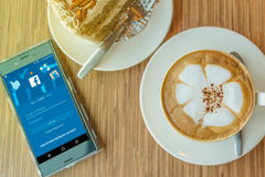 Мобильный телефон с начальным экраном применения Facebook и чашкой кофе Стоковое Изображение RF