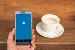 Мобильный телефон с начальным экраном применения Facebook и чашкой кофе Стоковые Изображения RF