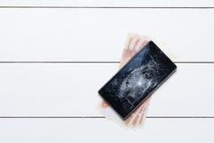 Мобильный телефон с сломленными экраном и деньгами на ремонте на поле Стоковое Фото
