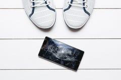 Мобильный телефон с сломленным экраном на деревянном поле Стоковое Изображение