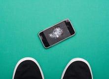 Мобильный телефон с сломленным экраном на поле Стоковая Фотография RF