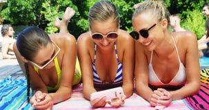 Мобильный телефон усмехаясь женщин используя пока отдыхающ poolside акции видеоматериалы