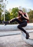 Мода города: портрет милой маленькой девочки нося черные джинсы, ботинки и тему сидит на трубе Стоковые Фотографии RF
