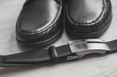 Мода людей Аксессуары людей Черные ботинки и черный пояс 1 жизнь все еще Взгляд дела на деревянной предпосылке Стоковое фото RF