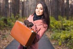 Мода, сезон и концепция людей - счастливая молодая женщина идет задействовать с ретро чемоданом на предпосылке осени стоковое фото