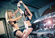 Модели на мытье автомобиля в гараже. Стоковое Фото