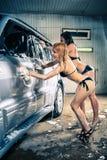 Модели на мытье автомобиля в гараже Стоковое Фото