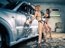 Модели на мытье автомобиля в гараже Стоковая Фотография