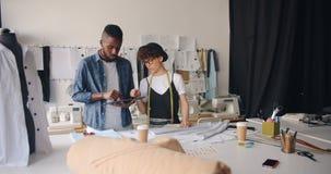 Модельеры девушки и парня измеряя ткань и используя планшет в студии сток-видео