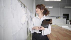 Модельер делая примечания пока смотрящ картины в шить студии акции видеоматериалы