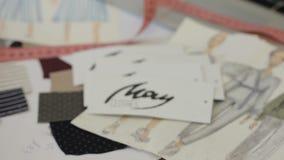 Модельер принимает чертежи одежд лежа на таблице, женщине профессионал работает на новом модном проекте видеоматериал
