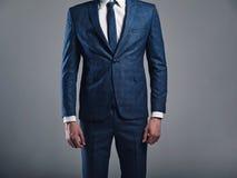 Модель бизнесмена красивой моды стильная одела в элегантном голубом костюме представляя на сером цвете стоковая фотография
