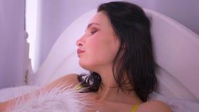 Модель брюнета в черном женском белье лежа на кровати сени под одеялом меха смотря мило в камеру видеоматериал