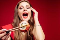 Модель брюнета молодая с длинными волосами есть азиатскую еду стоковое изображение
