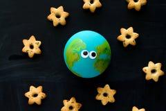 Модель взгляда сверху handmade планеты земли со смешными googly глазами и печеньями в форме звезд на доске, космосе и стоковые изображения