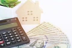 Модель деревянного дома, американские доллары получает деньги и калькулятор наличными на таблице Стоковое Фото