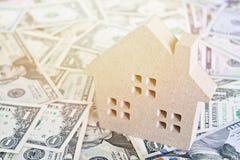 Модель деревянного дома на американских долларах получает деньги наличными Стоковое Изображение