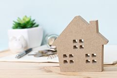 Модель деревянного дома перед монетками разбросанными от стеклянных опарника и копилки на деревянном столе Стоковая Фотография