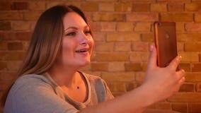 Модель добавочного размера женская имея видео- звонок на смартфоне и фиксируя ее волосы мило в уютной домашней атмосфере видеоматериал