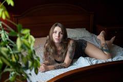 Модель добавочного размера сексуальная с татуировками лежит на большой кровати Стоковые Изображения RF