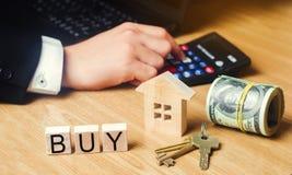 модель дома, ключи, доллары и ` надписи покупают ` на деревянных блоках приобретение квартиры, свойство доступное housi стоковое фото rf