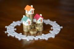 Модель 3 домов на монетках стога Мозаика, сохраняя деньги и концепция управления свойства, свойство вклада, страхование жилья стоковое изображение