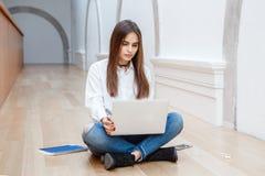 Модель женщины с длинными темными волосами в белой рубашке и голубых джинсах сидя на поле в зале в университете коллежа работая н Стоковое фото RF