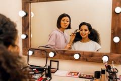 Модель и визажист смотря зеркало стоковая фотография