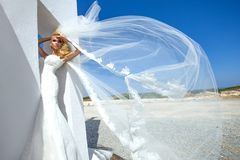 Модель красивой невесты белокурая женская в изумительном платье свадьбы представляет на острове Santorini в Греции Стоковые Фотографии RF